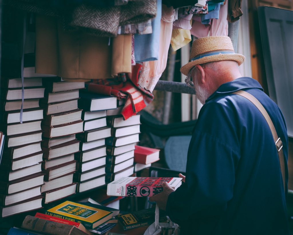 Man studying books in the market place assessing which is best